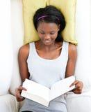 Adolescente femenino brillante que lee un libro en un sofá Fotografía de archivo libre de regalías