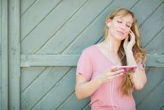 Adolescente femenino canta mientras que escucha la música en Smartphone Imagenes de archivo