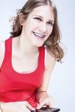 Adolescente femenino caucásico con los soportes de los dientes que charla por el teléfono móvil Fotografía de archivo libre de regalías