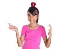 Adolescente femenino con Apple en su cabeza I Imagen de archivo libre de regalías