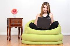 Adolescente femenino con el ordenador portátil Foto de archivo