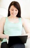 Adolescente femenino con la computadora portátil en su regazo Fotografía de archivo libre de regalías