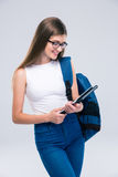 Adolescente femenino con la mochila usando la tableta Foto de archivo libre de regalías