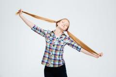 Adolescente femenino con los ojos cerrados que sostienen sus colas de caballo Foto de archivo libre de regalías
