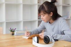 adolescente femenino de la muchacha asiática que estudia en la escuela Estudiante que escribe n Fotografía de archivo libre de regalías