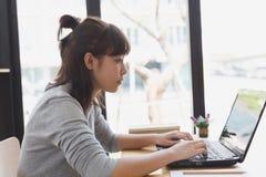 adolescente femenino de la muchacha asiática que estudia en la escuela Estudiante que mecanografía encendido Imágenes de archivo libres de regalías