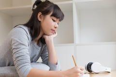 adolescente femenino de la muchacha asiática que estudia en la escuela Estudiante que miente y Fotografía de archivo