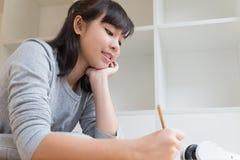 adolescente femenino de la muchacha asiática que estudia en la escuela Estudiante que miente y Imagen de archivo libre de regalías