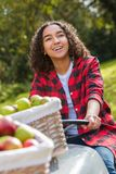 Adolescente femenino de la raza mixta que conduce manzanas de la cosecha del tractor Fotografía de archivo