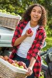 Adolescente femenino de la raza mixta que se inclina en el tractor que come Apple Imagenes de archivo