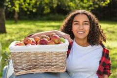 Adolescente femenino de la raza mixta que se inclina en manzanas de la cosecha del tractor Fotografía de archivo