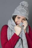Adolescente femenino de risa que sonríe en la ocultación debajo de la bufanda del invierno Foto de archivo libre de regalías