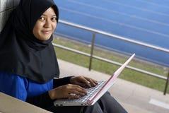 Adolescente femenino del Malay con la computadora portátil Foto de archivo