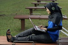 Adolescente femenino del Malay con la computadora portátil Imagen de archivo