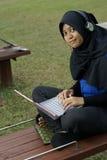 Adolescente femenino del Malay con la computadora portátil Foto de archivo libre de regalías