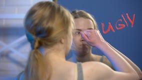 Adolescente femenino desesperado que limpia la palabra fea en la superficie del espejo, problema emocional metrajes