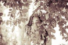 Adolescente femenino detrás de algunas hojas Foto de archivo libre de regalías