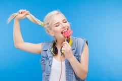Adolescente femenino elegante que come la piruleta Imagenes de archivo