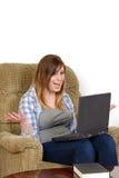 Adolescente femenino emocionado con el ordenador portátil Fotos de archivo libres de regalías
