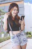 Adolescente femenino emocionado mientras que mira su teléfono Foto de archivo libre de regalías