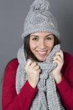 Adolescente femenino emocionado que se envuelve en bufanda suave del invierno Imagen de archivo