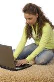 Adolescente femenino en la alfombra con la computadora portátil Fotografía de archivo libre de regalías