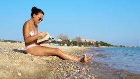 Adolescente femenino en la lectura del bikini en la playa Imagen de archivo libre de regalías