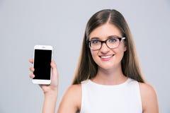 Adolescente femenino en los vidrios que muestran la pantalla en blanco del smartphone Fotos de archivo