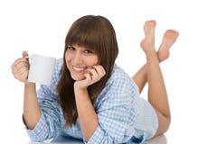 Adolescente femenino en pijamas con la taza de té Imagenes de archivo