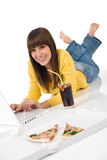 Adolescente femenino feliz con la computadora portátil que se acuesta Fotos de archivo