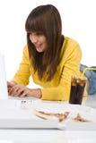Adolescente femenino feliz con la computadora portátil que se acuesta Imagen de archivo