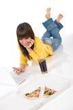 Adolescente femenino feliz con la computadora portátil y la pizza Fotos de archivo libres de regalías