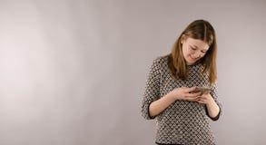Adolescente femenino feliz con un teléfono móvil Imágenes de archivo libres de regalías