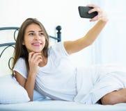 Adolescente femenino feliz que hace el selfie en cama Imagenes de archivo