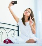 Adolescente femenino feliz que hace el selfie en cama Foto de archivo