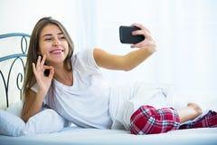 Adolescente femenino feliz que hace el selfie en cama Foto de archivo libre de regalías