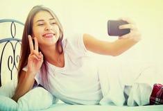 Adolescente femenino feliz que hace el selfie en cama Fotos de archivo libres de regalías