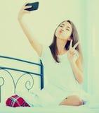 Adolescente femenino feliz que hace el selfie en cama Fotografía de archivo libre de regalías