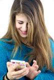 Adolescente femenino feliz que juega con mandar un SMS del teléfono celular Fotografía de archivo