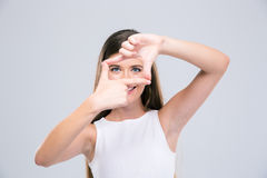 Adolescente femenino feliz que mira la cámara con gesto del marco Foto de archivo