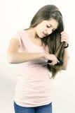 Adolescente femenino feliz que peina el pelo largo Foto de archivo libre de regalías