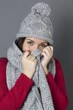 Adolescente femenino feliz que sonríe en la ocultación debajo de la bufanda del invierno Fotos de archivo libres de regalías