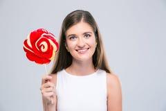 Adolescente femenino feliz que sostiene la piruleta Fotos de archivo