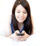 Adolescente femenino feliz que usa el teléfono celular en la cama Fotos de archivo