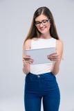 Adolescente femenino feliz que usa la tableta Imagen de archivo libre de regalías