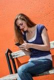 Adolescente femenino hermoso que mecanografía un mensaje de teléfono, usando comunicaciones en línea Fotos de archivo