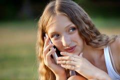 Adolescente femenino hermoso que toma en el teléfono al aire libre Foto de archivo libre de regalías
