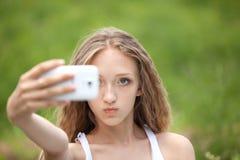 Adolescente femenino hermoso que toma un Selfie con el teléfono Imagen de archivo libre de regalías