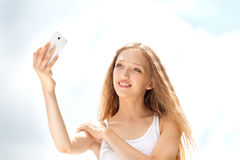 Adolescente femenino hermoso que toma un Selfie con el teléfono Foto de archivo libre de regalías