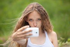 Adolescente femenino hermoso que toma un Selfie con el teléfono Imágenes de archivo libres de regalías
